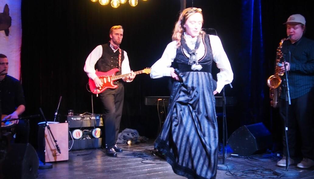 Her er Marianne Haugli i jubileumsdrakten for Oslo på scenen, herredrakten skimtes bak.